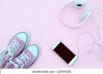 Smartphone mock up template with sneakers and cool headphones. View from above. Flat lay.PInk