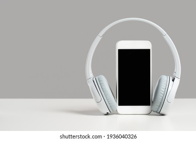 Smartphone mockup display with grey wireless headphones on white desk gray background. Copy space. Audio technology apps, music podcasts books