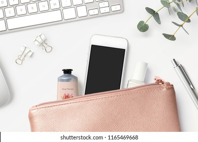 smartphone mock-up with rose gold clutch bag, cosmetics, office tools, keyboard and eucalyptus twigs on a white feminine styled desk - flat lay / top view