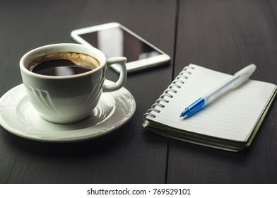 Smartphone with notebook and cup of coffee on dark wooden table