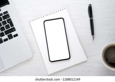 Smartphone and notepad on wooden table
