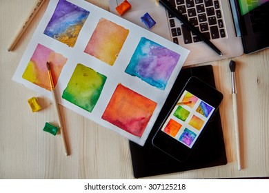 smartphone on arts hand drawn background with digital artist supplies: brushes, laptop, paper