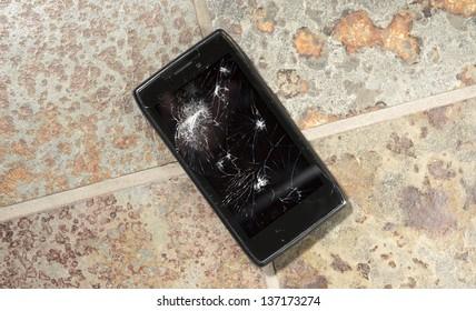 Smartphone on hard floor with cracked screen.