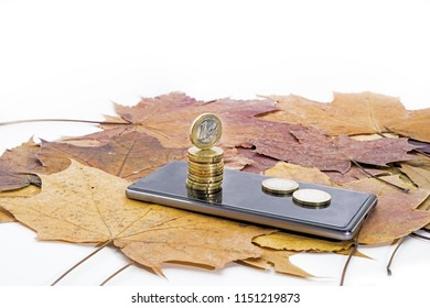 Smartphone on maple leaves background with some coins. Autumn abstraction.