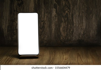 Smartphone on a stand and vintage wooden desk as a background. Mockup to promote your mobile app on the blank screen