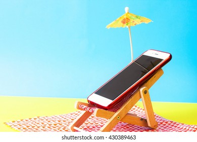Smartphone on a sunbed on the beach. Holiday without smartphone concept.