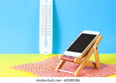 Smartphone on a sunbed on the beach with thermometer in the background. Holiday without smartphone concept.