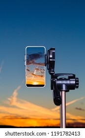 Smartphone on tripod capturing image of stunning sundown in vertical mode