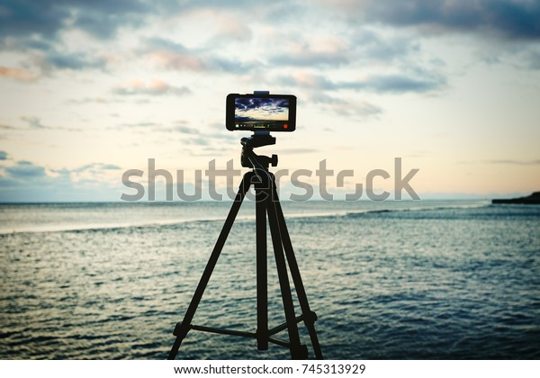 Smartphone on tripod capturing seascape sunrise timelapse. Mobile photography or videography concept.