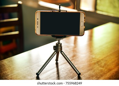 Smartphone on a tripod in living room with clipping path at screen inside