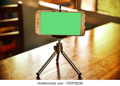 Smartphone on a tripod in living room with clipping path at visual green screen inside