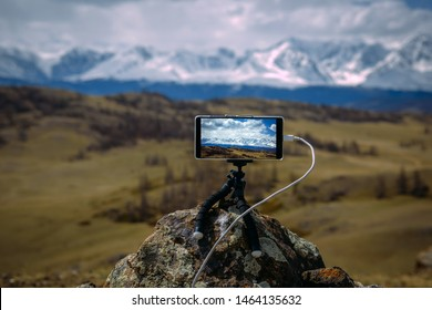 Smartphone on tripod mounted on stone in front of  stunning view of the snow-capped peaks. Image is focused on display. Gadget records timelapse of moving of clouds over the North Chui mountain range.