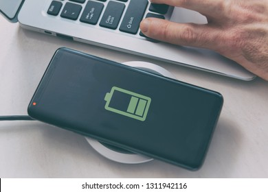 Smartphone on a wireless charging pad, charger.