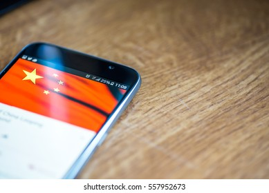 Smartphone on wooden background with 5G network sign 25 per cent charge and China flag on the screen.