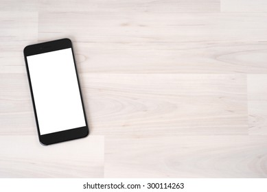 Smartphone on wooden table on light background
