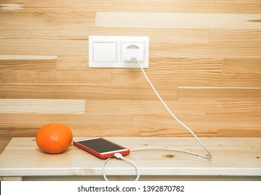 Smartphone and orange are lying on the bedside table. Stylish minimalist photo. Mobile is charging.