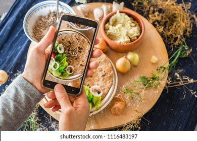 Smartphone photo of food. Woman hands make phone photography of Indian traditional bread. Garlic naan with vegetables for lunch or dinner. For social media, blogging. Raw vegan vegetarian healthy food