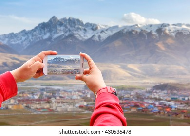 Smartphone photographing Village inclose mountain a famous landmark in Ganzi, Sichuan, China.