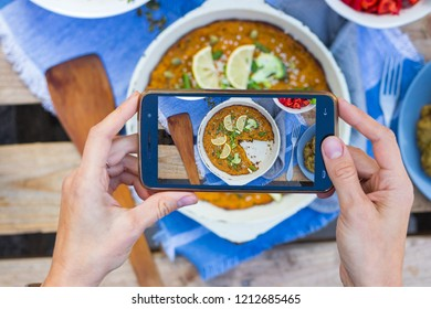 Smartphone photography of food. Woman hands holds mobile phone and take or make beautiful trendy food photo for social networks or blogging. Pumpkin casserole with broccoli.