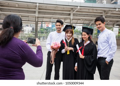 Smartphone photography of two happy couple to celebrate Commencement day. Success education concept. Female garduated students in black graduation gowns with boyfriends.