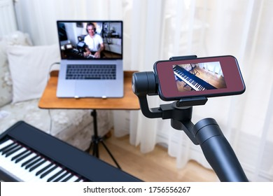 A smartphone placed on a gimbal used as second camera for online piano lesson. DIstance music education setup