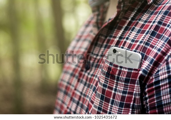 Smartphone in a plaid shirt chest pocket