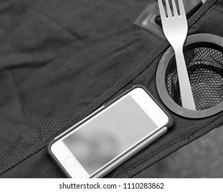Smartphone and plastic fork on camp chair
