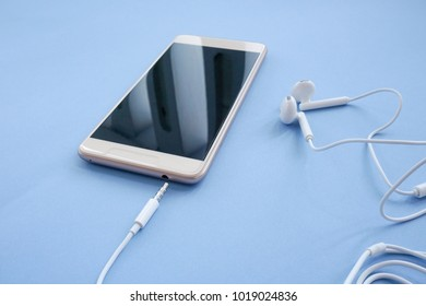 Smartphone is Plugged in with Earphones 3.5 mm Jack on Blue Background