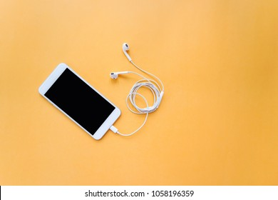 Smartphone Plugged in with Earphones on Orange Background Top View