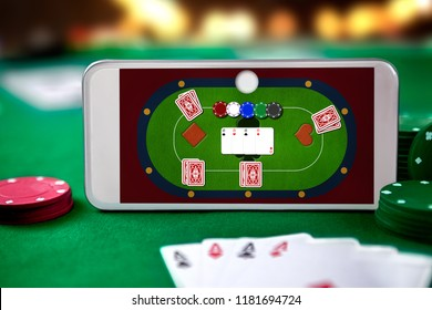 Smartphone with poket table on screen, playing cards and chip cards on poker table. Online casino.