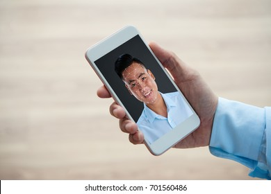 Smartphone with polygonal grid on face of smiling Vietnamese man