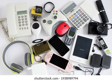 Smartphone with portable game consoles and ebook reader and other obsolete electronic gadgets on white background,Top view, Reuse and Recycle concept,