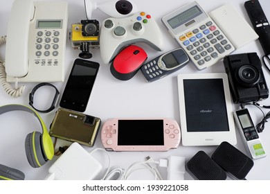 Smartphone with portable game consoles and ebook reader and other obsolete electronic gadgets on white background, With copy space for text, Top view, Reuse and Recycle concept