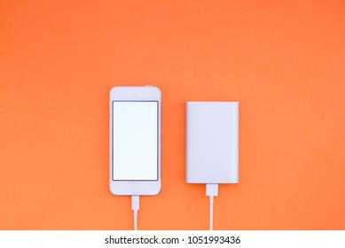 Smartphone and Powerbank on orange background. Powerbank charges the phone against the background. Flat lay