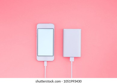 Smartphone and Powerbank on pink background. Powerbank charges the phone against the background. Flat lay.