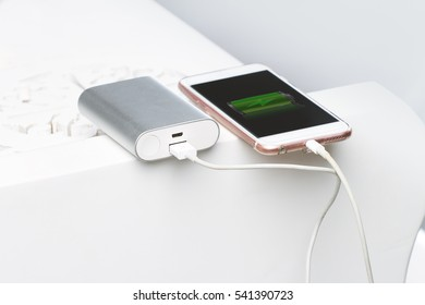 Smartphone and powerbank. s a symbol of mobile energy and electric equipment in modern design