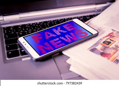 Smartphone with red Fake News words on screen over a newspaper. HOAX and Fake news concept.