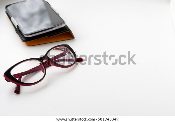Smartphone and red glasses on a light background