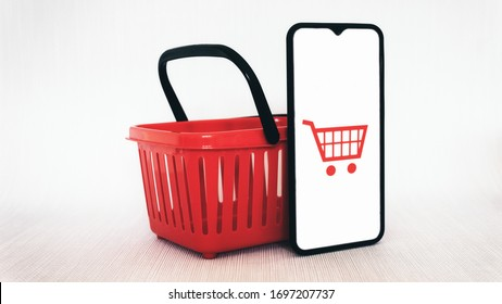Smartphone and red shopping basket online shopping and home delivery concept mockup