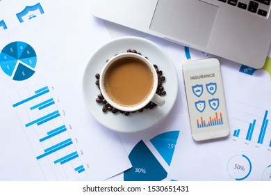 Smartphone to search for insurance online and Coffee, Document, Laptop on desk in the morning.  Insurance concept