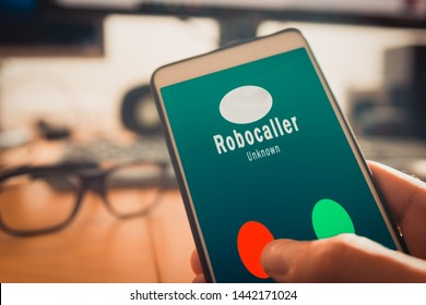Smartphone showing on screen an illegal robocall. Smartphone showing a call from a robocaller on screen