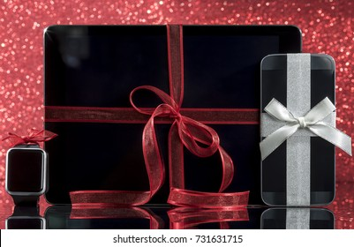 Smartphone and smartwatch and tablet pc with decorations for Christmas tree on black glass table over red background. Focus on smartphone.