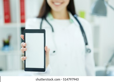 Smartphone with space for text or image in the hand of female doctor. Medical advertisement concept. Photo with depth of field.