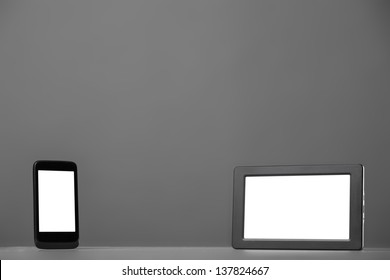 Smartphone and tablet computer on a gray background.