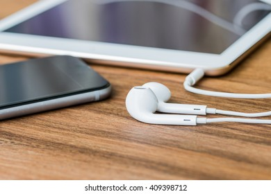 Smartphone tablet with earphones on wooden background