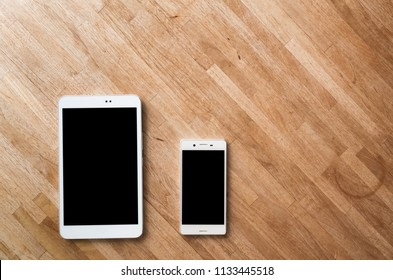 smartphone and tablet on wooden desk with nobody
