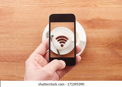 Smartphone taking photograph of free wifi sign on a latte coffe in a bar