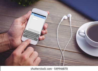 Smartphone text messaging against person holding smart phone at desk