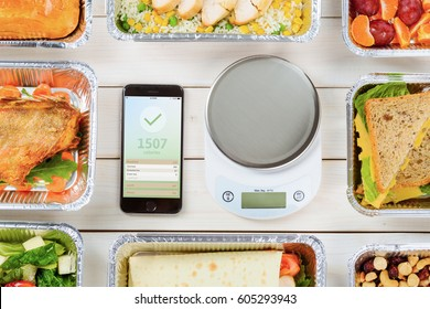 Smartphone with a weight loss app and a food scale on the wooden surface. Lean fish, a vegetable roll, cashews and hazelnuts, salad, a pie, chicken and fresh fruit. Count calories.
