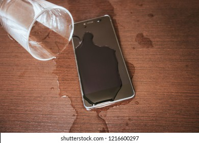 Smartphone wet by accident on wooden table. Glass of water spilled.